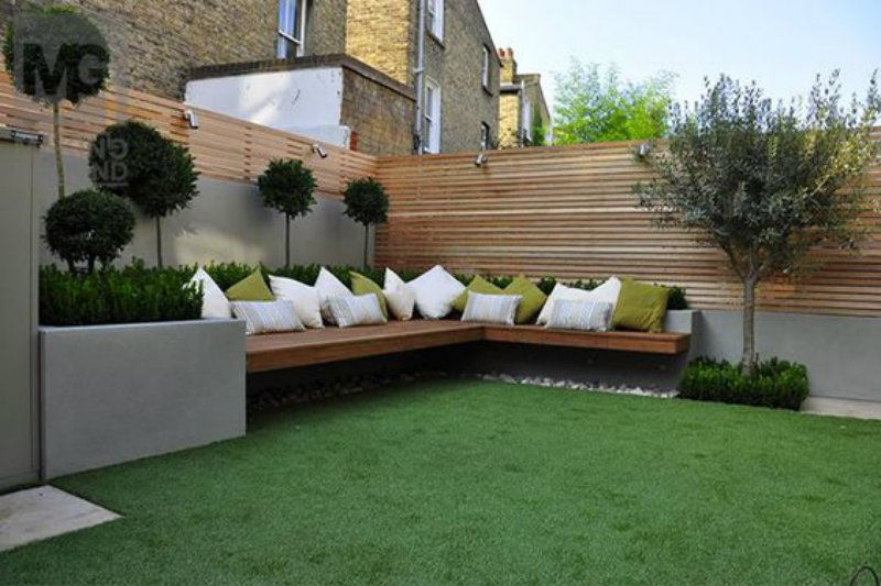 Artificial Grass Garden Designs beige limestone paving hardwood privacy screen trellis fence horizontal slats raised render beds fake artificial grass Because Of This It Can Be An Ideal Choice For Someone Who Loves To Throw Garden Parties But Hates The Drawn Out Cleaning That Comes Afterwards Astroturf